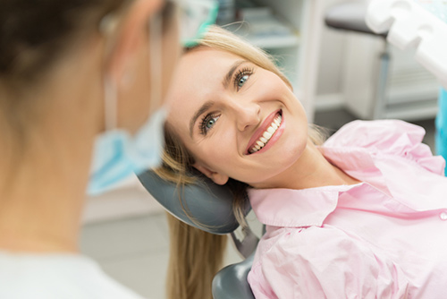 Female patient smiling while relaxing in dental chair and speaking with oral surgeon at Pacific Maxillofacial Center